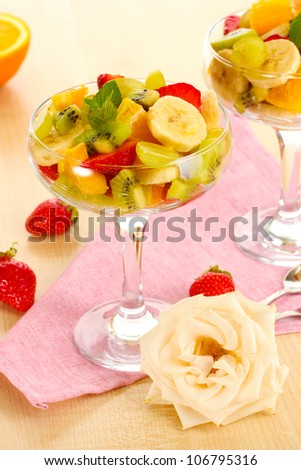 Fresh fruits salad and strawberries on wooden table