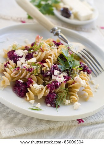 Fresh fusilli pasta with beet pesto and cheese. Selective focus