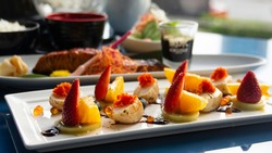 fresh fusion food. colorful dishes of giant scallops with strawberry and sunquick orange. Asian fusion food