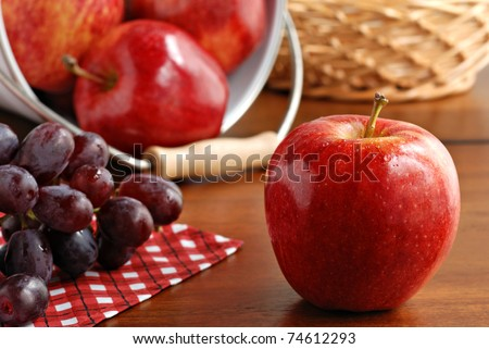 Fresh gala apple with grapes on wood table.  Additional apples spilling from bucket in background.  Macro with shallow dof.