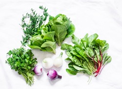 Fresh garden herbs on a white background, top view. Spinach, coriander, romaine salad, red onion - delicious aromatic food ingredients