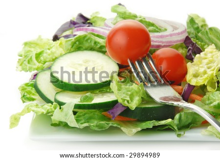 Fresh garden salad with lettuce onion tomato cucumber on white background.