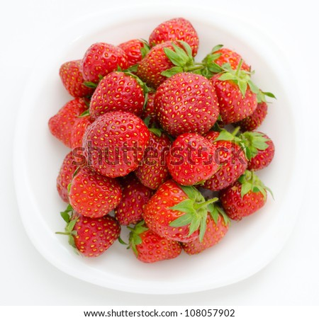 fresh garden strawberries on a white plate, top view - stock photo