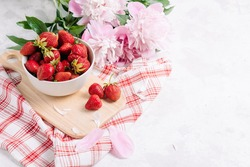 Fresh garden strawberry in a plate on a wooden kitchen board with a beautiful napkin and serving, wholesome food and vitamins, diet. Pink and white peony flowers, side view