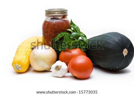 Fresh garden vegetables and also a jarred of canned tomatoes on white background.