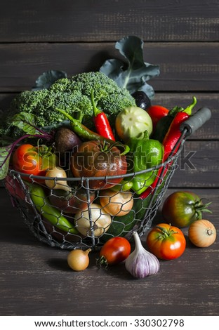 fresh garden vegetables - broccoli, zucchini, eggplant, peppers, beets, tomatoes, onions, garlic - vintage metal basket on a wooden background - Shutterstock ID 330302798