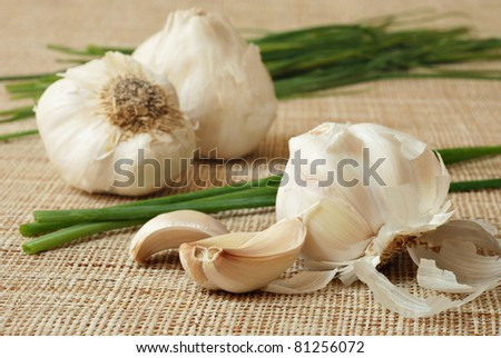 Fresh garlic and chives on natural textured fabric.  Macro with shallow dof.  Selective focus on cloves.