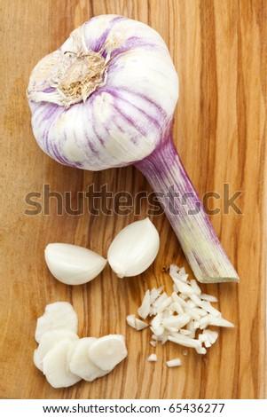 fresh garlic bulb, cloves and chops on wooden cutting board