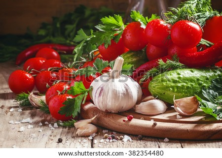 Fresh garlic, cherry tomatoes, cucumber, hot pepper, parsley, dill on a wooden cutting board, vegetables for the Mediterranean diet, selective focus #382354480