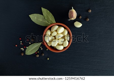 Fresh garlic heads, cloves set on a black stone surface, top view, copy space, copy space for text.