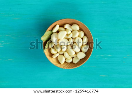 Fresh garlic heads, cloves set on a blue turquoise wooden surface, top view, copy space, copy space for text.