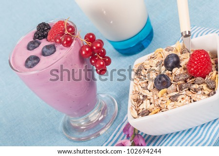Fresh glass of delicious yogurt with berries and muesli
