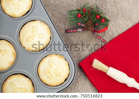 Fresh golden brown mince pies in a baking tray with a christmas motif and a pastry brush on a red napkin