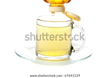 fresh golden honey being dripped into a clear glass tea cup of fresh brewed tea, isolated on white with room for your text - stock photo