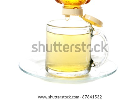 fresh golden honey being dripped into a clear glass tea cup of fresh brewed tea, isolated on white with room for your text