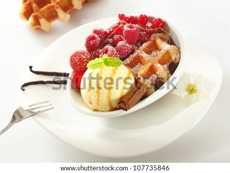 Fresh golden waffle served with icecream and an assortment of red berries including raspberries, redcurrants and strawberries