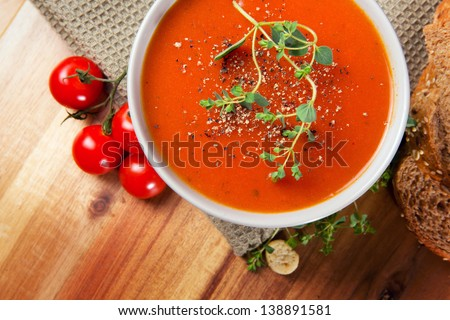 Fresh gourmet tomato soup with fresh herbs and pepper. Bread, oregano and tomatoes on the side.