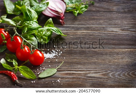 Fresh grape tomatoes with basil, spices and coarse salt on wooden board with copy space.