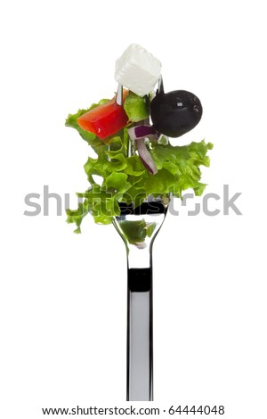 fresh greek salad consisting of lollo bionda lettuce, black olive, sheep cheese, red onion and tomato sticking on fork, isolated on white