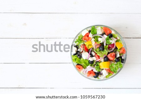 Fresh Greek salad in a bowl on wooden table, top view.