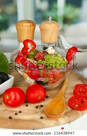 Fresh greek salad in glass bowl surrounded by ingredients for cooking on wooden table on window background close-up