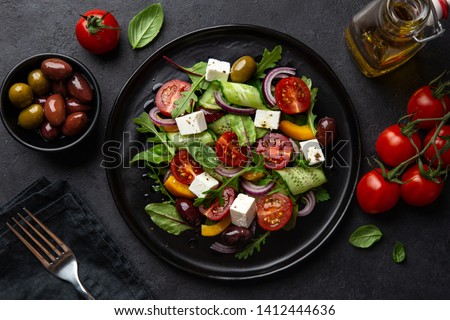 Fresh greek salad with tomato, cucumber, bel pepper , olives and feta cheese on black plate, top view, dark background