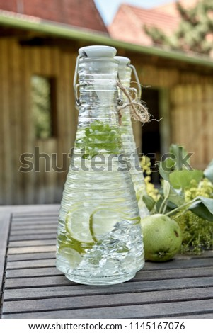 Fresh green apple and herb infused water in decorative conical glass bottles on a rustic wooden table outdoors