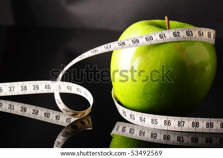 fresh green apple and tapeline - stock photo