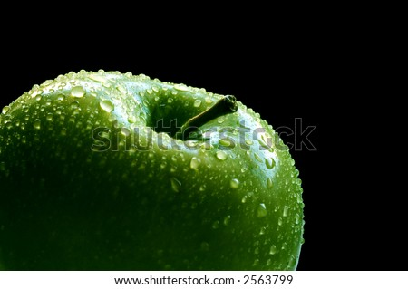 Fresh green apple closeup over black background