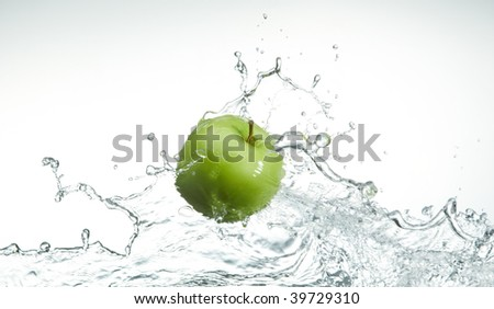 fresh green apple on water level with splash