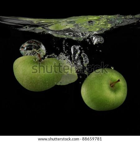 Fresh green apples splashing into the water