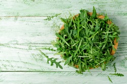 Fresh green arugula in bowl on wooden table. Arugula is rich in vitamins and trace elements