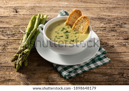 Fresh green asparagus soup in bowl on wooden table Stock photo ©
