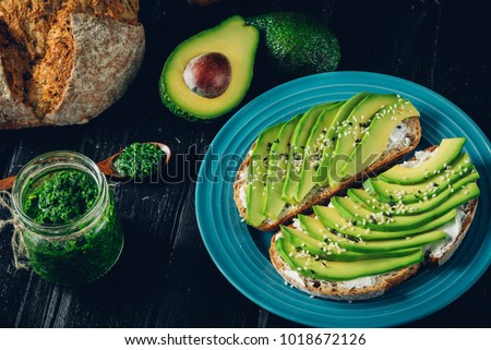 Fresh green Avocado sandwich on dark rye bread made with fresh sliced avocados from above. Avo toast, avo sandwich