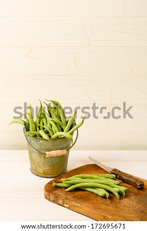 Fresh green beans sit in a bucket by a wooden cutting board with several green beans ready to be cut and cooked for a healthy dinner.  Open copy space above the image.