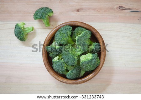 Fresh green broccoli in wood bowl over rustic wooden background - healthy or vegetarian food concept Top view. #331233743