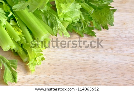 Fresh green celery on a wooden cutting board.