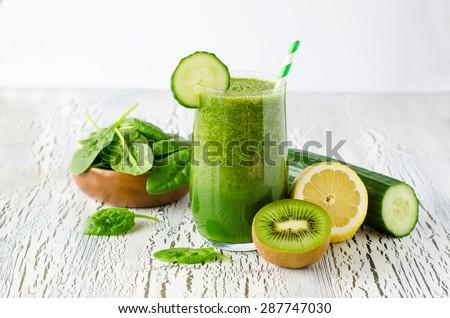 Fresh green detox smoothie on white wooden background, diet and health concept, vitamins