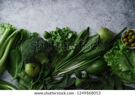 Fresh green food, variety of vegetables, greens and fruits on concrete textured background with copy space. Healthy eating concept. Monochromatic idea. #1249868053