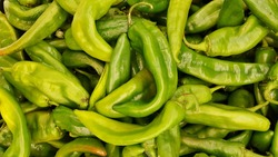 Fresh green Hatch Chili peppers in a traditional vegetable market in Houston, TX closeup image.