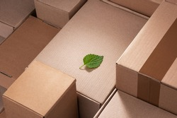 Fresh green leaf laying between cardboard boxes. Shipping deliveries, global trade and environmental impact.