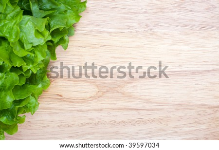 Fresh green lettuce on wooden board with space for text