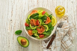 Fresh green lettuce salad with smoked salmon and avocado on wooden background