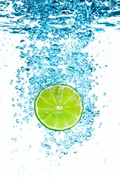 Fresh green lime in the clear water on white background.