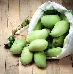 Fresh green mango with white plastic sack on wood