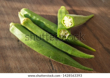 Fresh green okra on the wood table with sun light. Cross section of green okra.