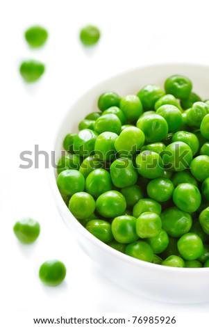 Fresh green peas in a white ceramic bowl.