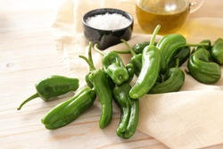 Fresh green pimientos or padron peppers, olive oil and coarse sea salt on a napkin and a light wooden table, ingredients for a Spanish tapa dish, copy space, selected focus, narrow depth of field