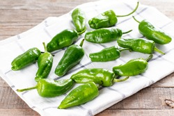 Fresh green pimientos or padron peppers on a napkin ready to be cooked. Spanish cuisine. Pimientos de Padron.