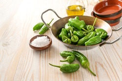 Fresh green pimientos or padron peppers, sea salt, olive oil and empty Spanish tapa bowls on a light wooden table, copy space, selected focus, narrow depth of field